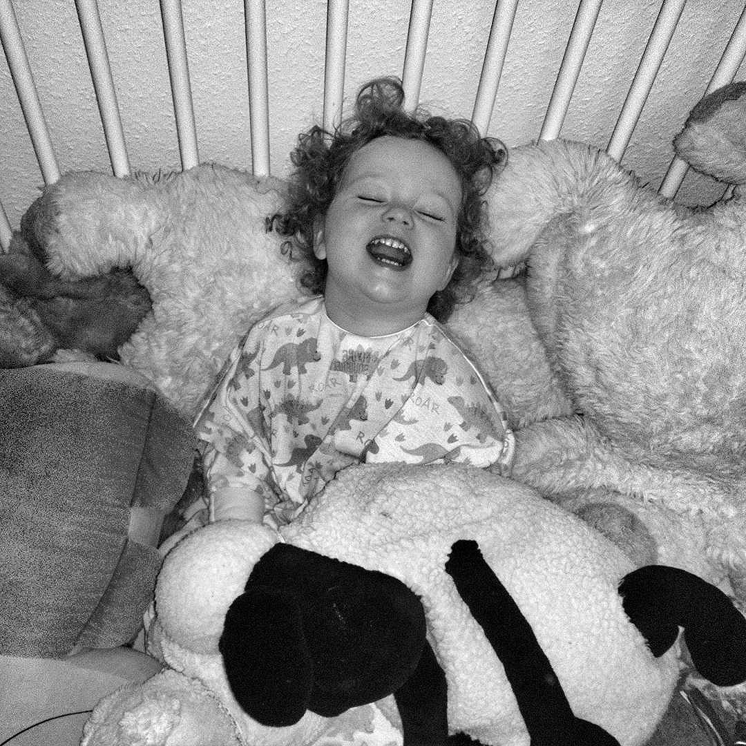 "My precious girl having a mightily grand auld time in her cot with all the . . . . This is her ""posed"" smile!"